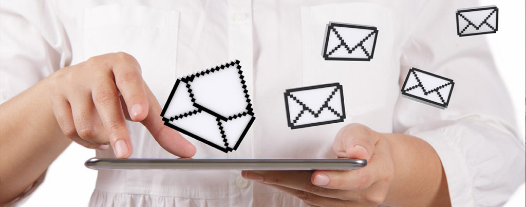 Person in white shirt working on a tablet with white mail icons floating above it