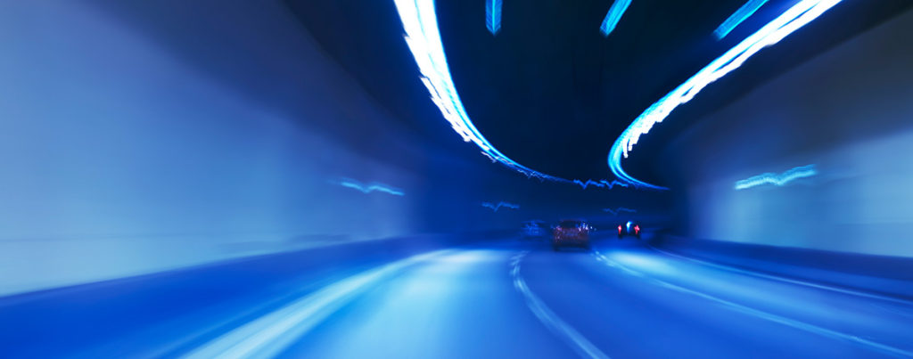 Blurred cars driving quickly through a tunnel