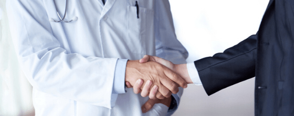 Doctor shaking hands with a man in a suit jacket