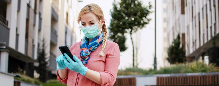 Woman wearing a mask and gloves while scrolling through a black cell phone