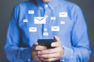 Man in blue shirt working on phone with white mail icons floating above it