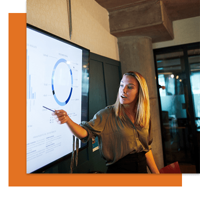 Blonde woman pointing at screen with data