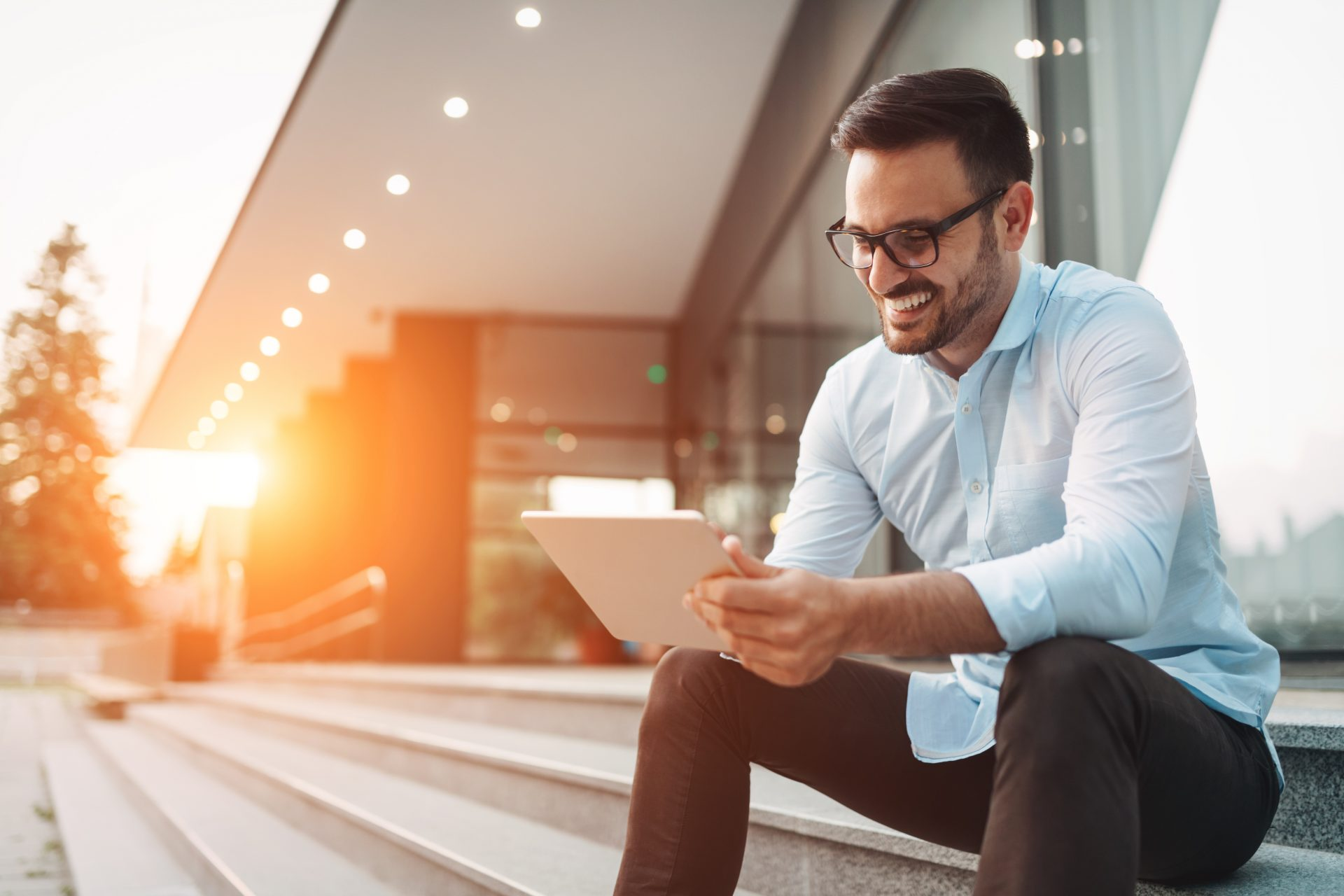 Man sitting outside smiling while working on tablet
