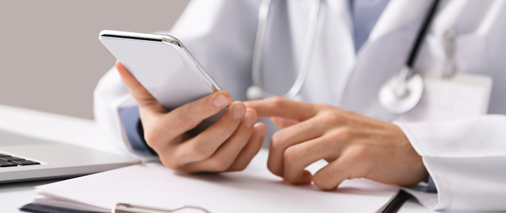 Doctor with stethoscope typing on a smartphone