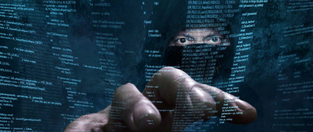 Hacker in mask reach hand out to steal data superimposed on screen