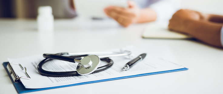 Stethoscope on top of clipboard while a doctor and a patient communicate in the background